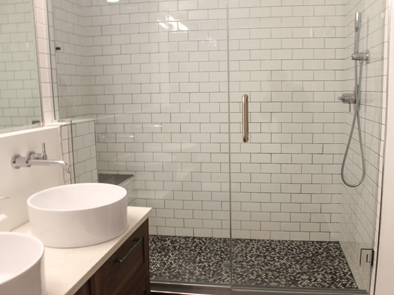 white subway tile shower with gray penny tile mosaic flooring