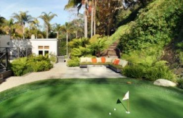 a putting green in a backyard of a home