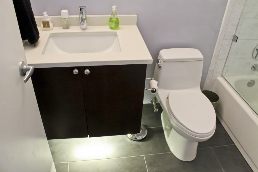 123 Remodeling bathroom project using underneath vanity lighting with wood style ceramic tile flooring.