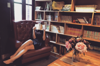 woman reading in large armchair next to bookshelf