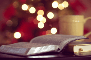 open book with coffee mug and fairy lights