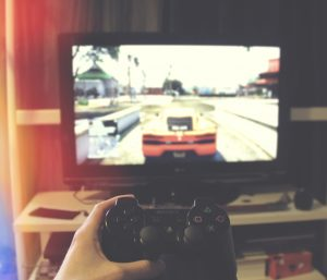 hands with a videogame controller playing a racing game