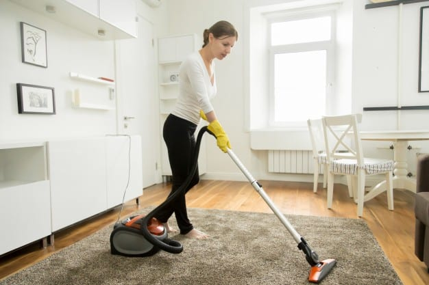 woman vacuum cleaning the carpet