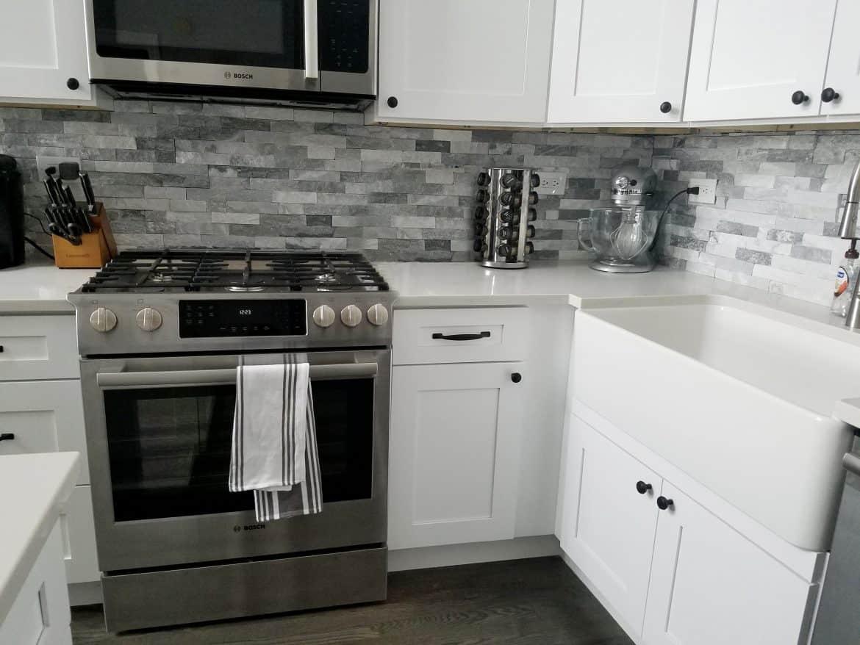 transitional white kitchen with grey subway backsplash