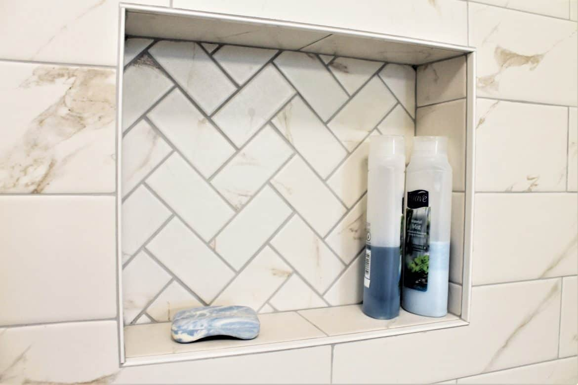 shower niche with white marble subway tiles and bullnose trim