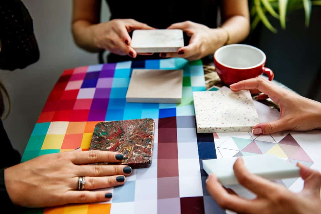 three women comparing several tile samples